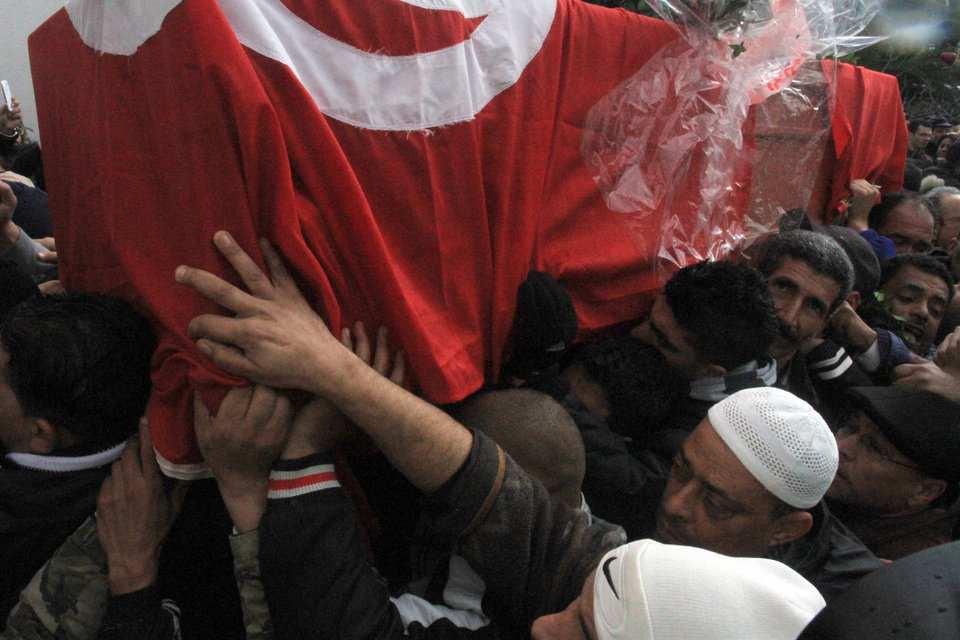 Photo - Tunisian men carry the coffin of slain opposition leader Chokri Belaid wrapped in the Tunisian red flag as they leave his father's house prior to his funeral in Tunis, Friday, Feb. 8, 2013. Tunisia braced for clashes on Friday, with the capital shut down by a general strike and the army deployed for the funeral of a slain opposition leader expected to draw tens of thousands of mourners, and potentially many more. (AP Photo/Amine Landoulsi)