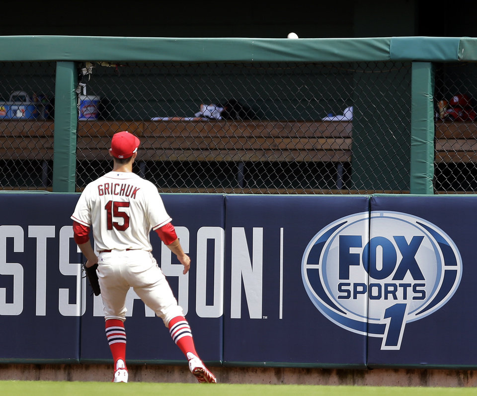 Photo - St. Louis Cardinals right fielder Randal Grichuk watches as a ball hit by Chicago Cubs' Logan Watkins clears the outfield fence for a solo home run during the fourth inning in the first baseball game of a doubleheader Saturday, Aug. 30, 2014, in St. Louis. (AP Photo/Jeff Roberson)