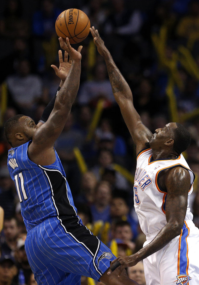 Photo - Oklahoma City's Kendrick Perkins (5) defends against Orlando's Glen Davis (11) during the NBA basketball game between the Oklahoma City Thunder and the Orlando Magic at the Chesapeake Energy Arena, Sunday, Dec. 15,  2013. Photo by Sarah Phipps, The Oklahoman