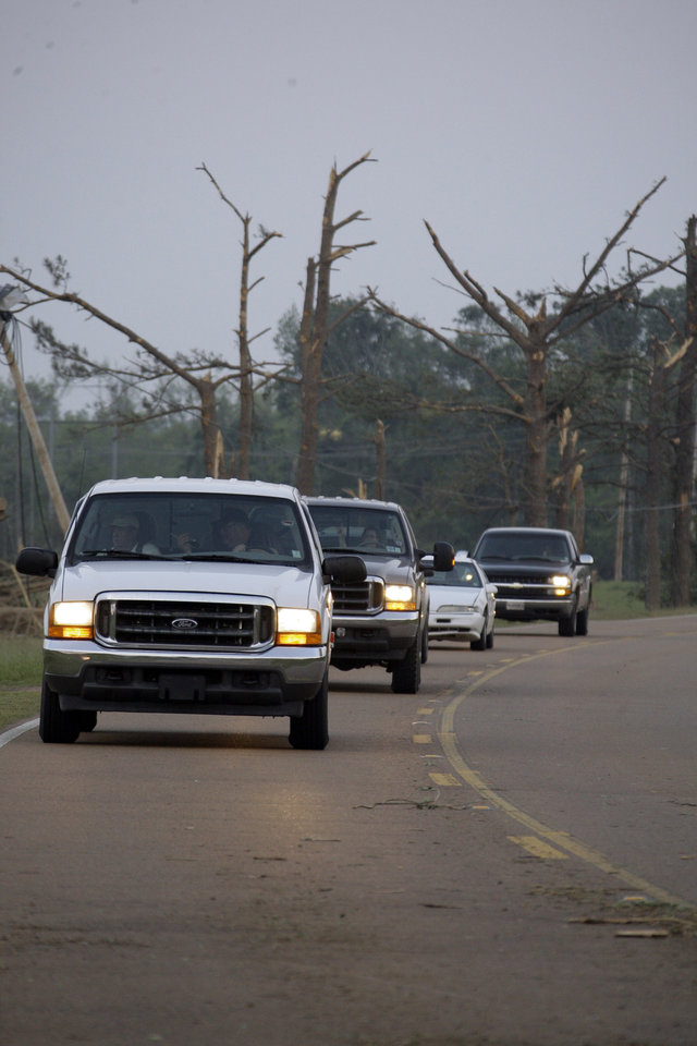 Photo - Residents drive past stripped pine trees from a tornado that passed through  Philadelphia,  Miss., Wednesday, April 27, 2011. Several tornadoes hit  in the state resulting in number of deaths. A wave of tornado-spawning storms strafed the South on Wednesday killing at least 77 people in four states.  (AP Photo/Rogelio V. Solis)