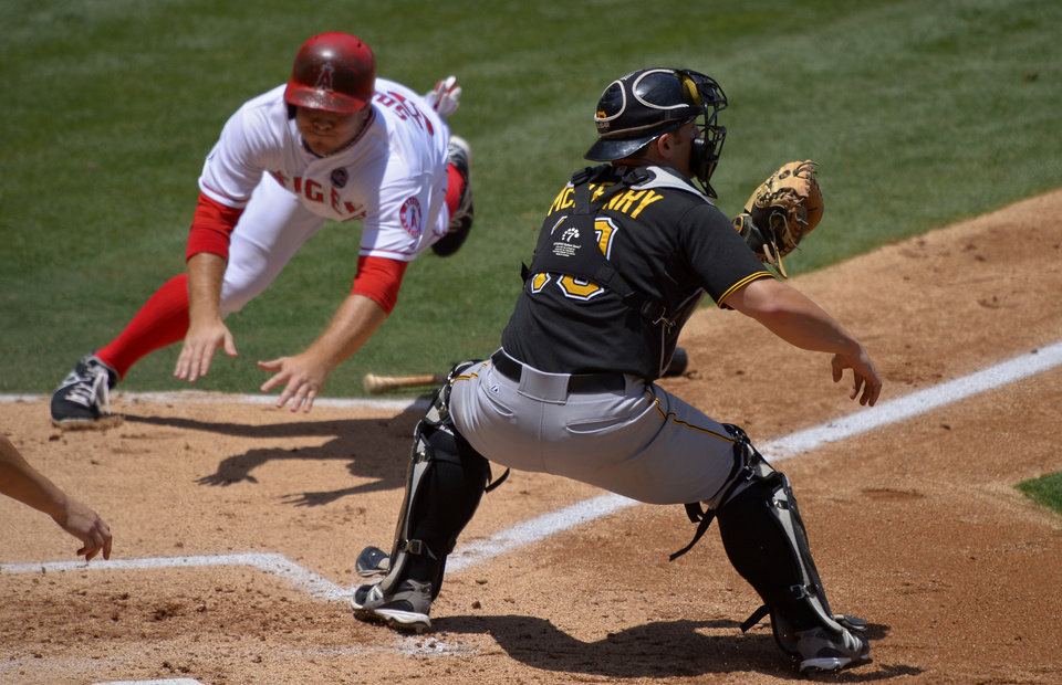 Photo - Los Angeles Angels' J.B. Shuck, left scores on a fielders choice by Mike Trout as Pittsburgh Pirates catcher Michael McKenry takes a late throw during the second inning of their baseball game, Sunday, June 23, 2013, in Anaheim, Calif.  (AP Photo/Mark J. Terrill)