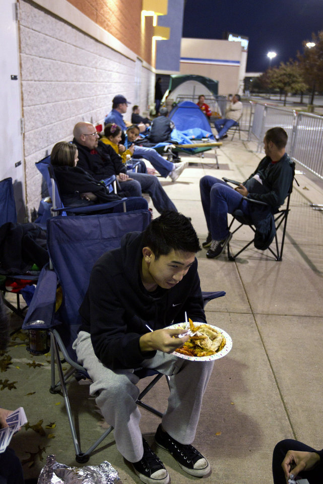 Photo -   Khang Nguyen, of Arlington, Texas eats his Thanksgiving dinner while waiting in line at a Best Buy store in Grapevine, Texas on Thursday, Nov. 22, 2012. Despite a surge of resistance as the sales drew near, with scolding editorials and protests by retail employees and reminders of frantic tramplings past, Black Friday's grip on America may be stronger than ever. (AP Photo/Star-Telegram/Joyce Marshall)