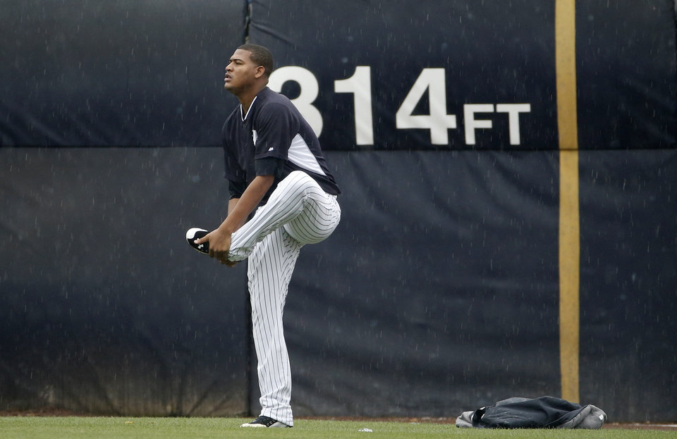 Photo - New York Yankees starting pitcher Ivan Nova warms out in the outfield before a spring exhibition baseball game against the Miami Marlins in Tampa, Fla., Saturday, March 29, 2014. Nova had been scheduled start Saturday, but rain forced the game to be canceled. (AP Photo/Kathy Willens)