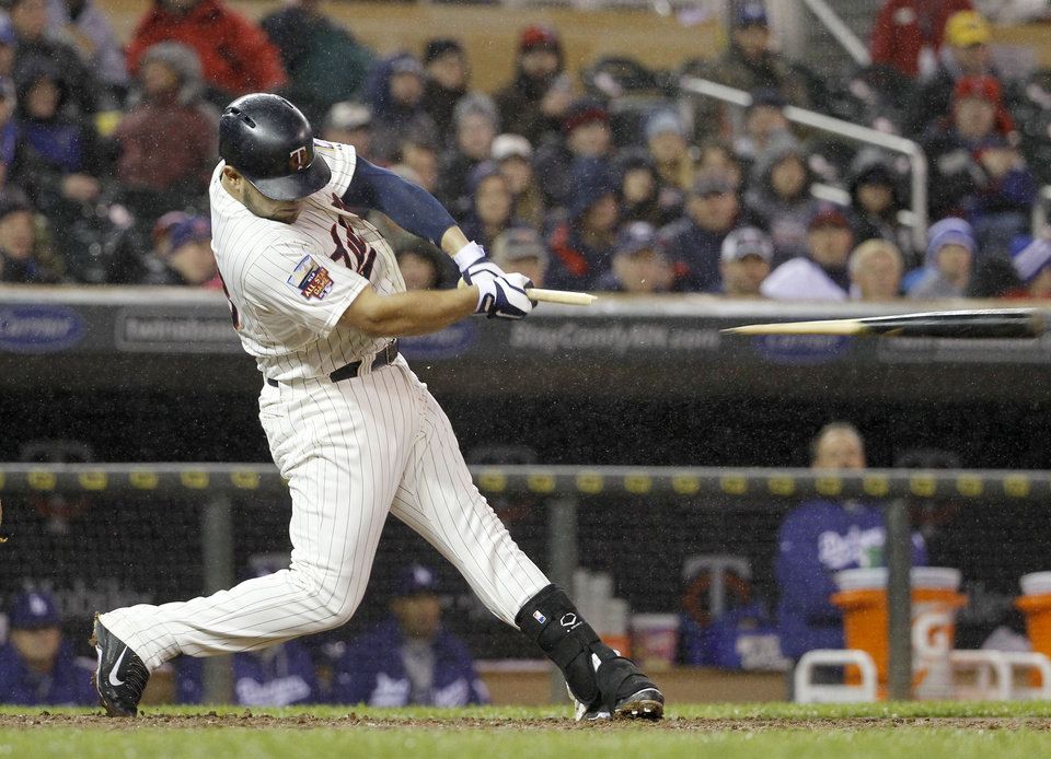 Photo - Minnesota Twins' Josmil Pinto breaks his bat on a single hit off Los Angeles Dodgers starting pitcher Zack Greinke during the fourth inning of a baseball game in Minneapolis, Wednesday, April 30, 2014. (AP Photo/Ann Heisenfelt)