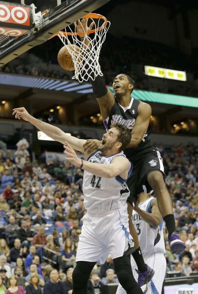 Photo - Sacramento Kings forward Jason Thompson, top, lands on Minnesota Timberwolves forward Kevin Love (42) as they battle for a rebound during the first quarter of an NBA basketball game in Minneapolis, Sunday, March 16, 2014. (AP Photo/Ann Heisenfelt)