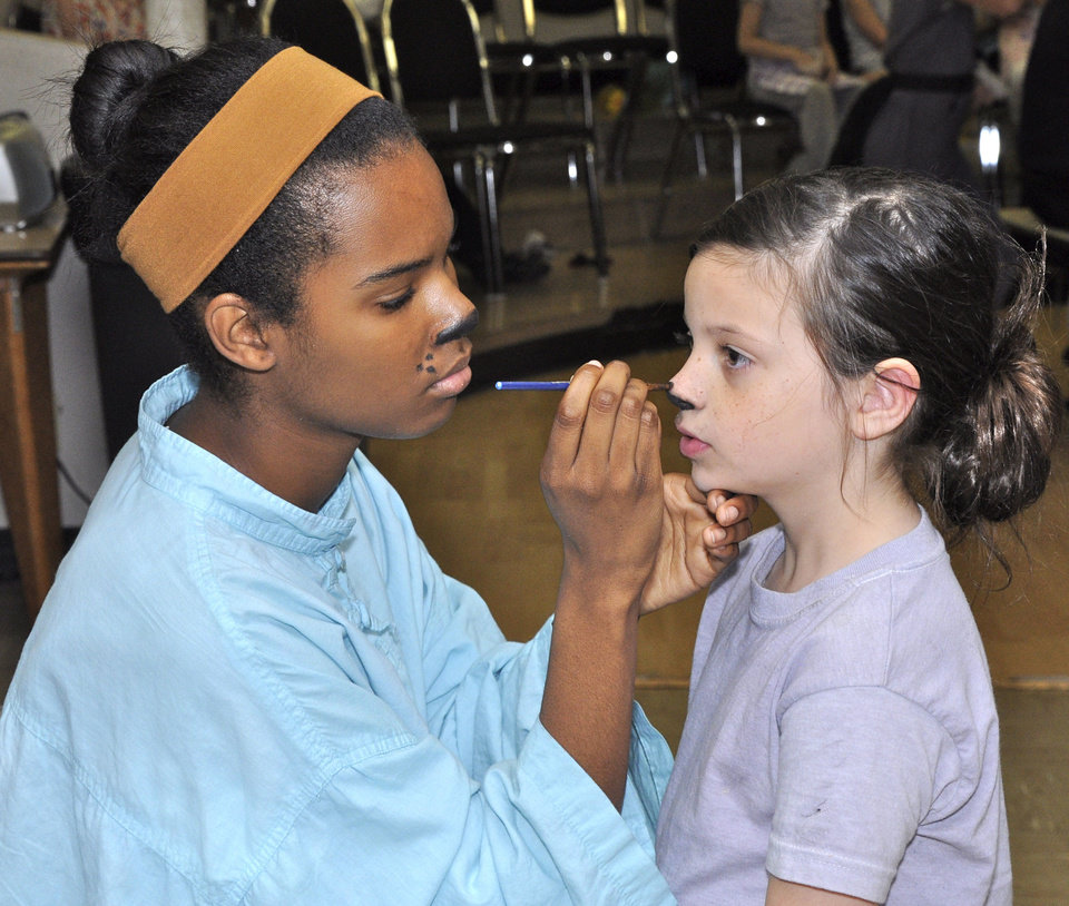 Photo - Hellen Smith applies makeup to the face of Isabel Charnceco backstage at Poteet Theater as the cast and crew readies for a performance of