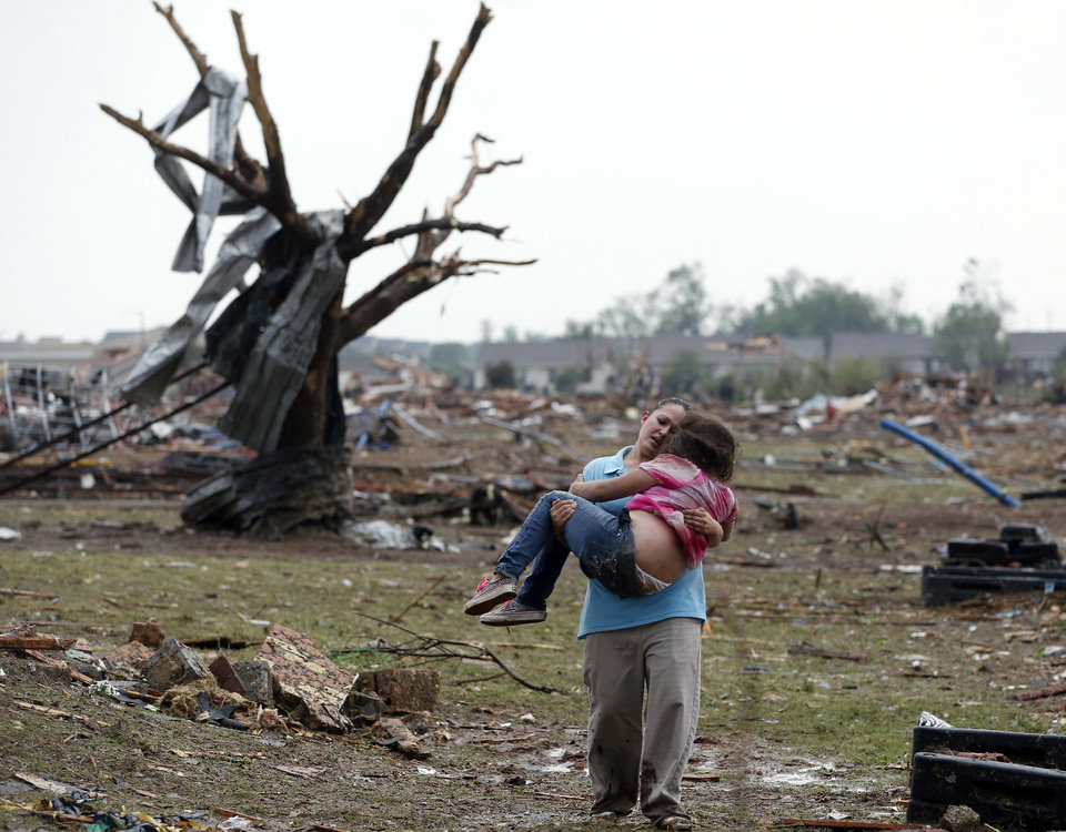Photo - CORRECTS TORNADO MEASUREMENT TO NUMBER REPORTED BY THE NATIONAL WEATHER SERVICE - A woman carries a child through a field near the collapsed Plaza Towers Elementary School in Moore, Okla., Monday, May 20, 2013.  A tornado as much as half a mile wide with winds up to 200 mph roared through the Oklahoma City suburbs Monday, flattening entire neighborhoods, setting buildings on fire and landing a direct blow on an elementary school. (AP Photo Sue Ogrocki)