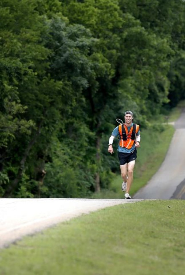 Photo -  James Strahorn runs on North Air Depot Boulevard in Edmond on Tuesday. Strahorn, the new cross country coach at Edmond North High School, is running across Oklahoma from the Kansas border to the Texas border. [Sarah Phipps/The Oklahoman]