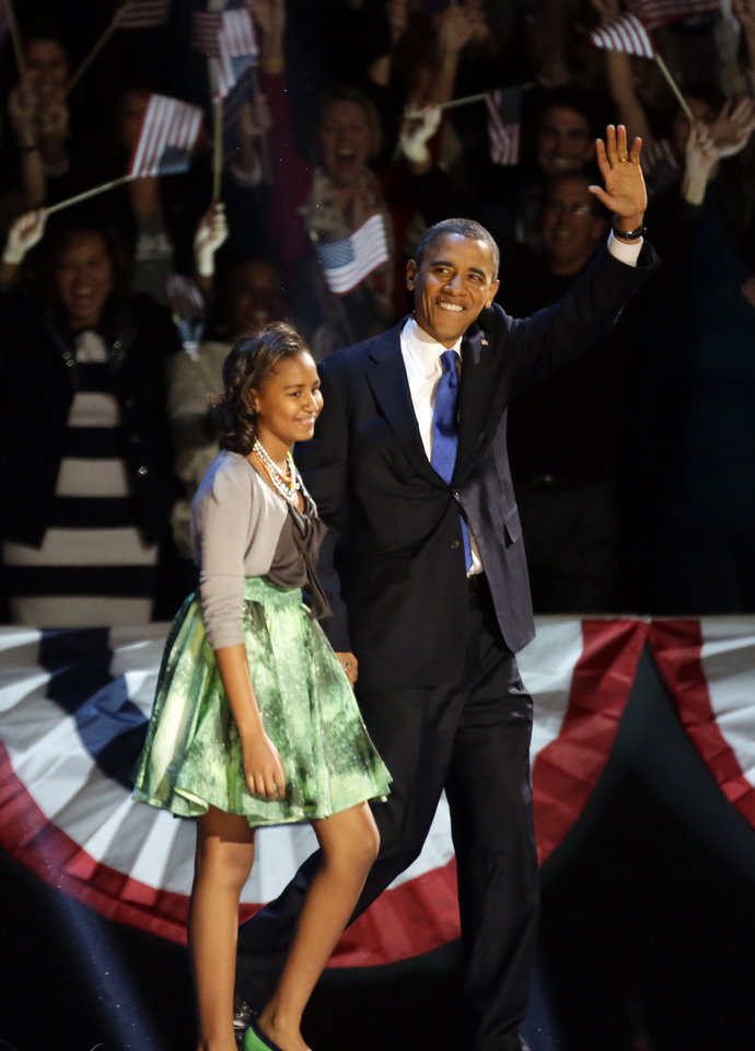 President Barack Obama waves as he walk on the stage with his daughter Malia at his election night party Wednesday, Nov. 7, 2012, in Chicago. President Obama defeated Republican challenger former Massachusetts Gov. Mitt Romney. (AP Photo/Pablo Martinez Monsivais)