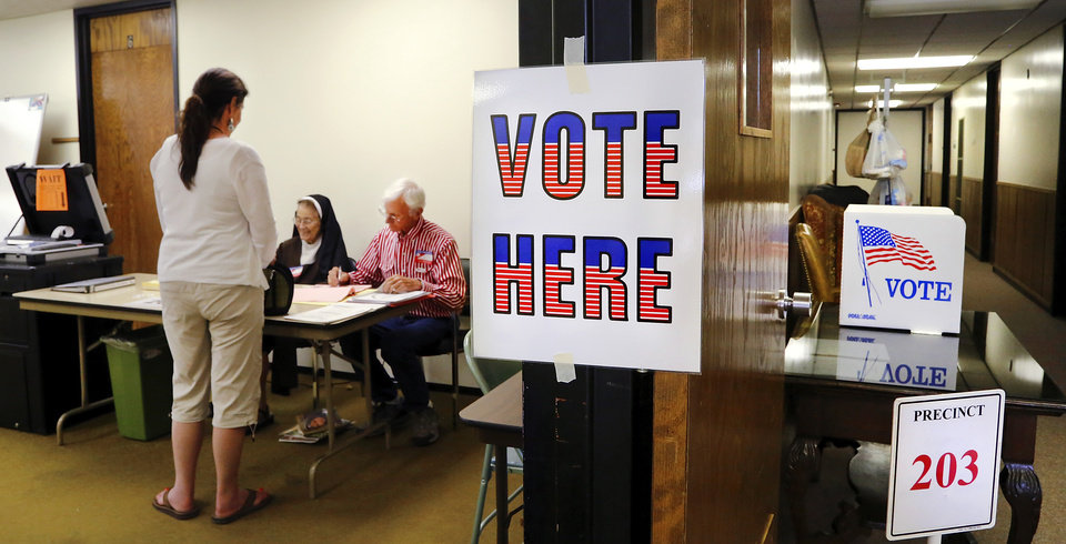 Photo - A voter waits to receive her ballot at election site for precinct  203 at Trinity Baptist Church, on NW 23 just west of Classen Blvd., on Tuesday, June 28, 2016. Polling workers are Sister Maria Francesca, a Catholic Carmelite nun, and Ed Reeve. Both said they have served as poll workers for more than 10 years. Photo by Jim Beckel, The Oklahoman