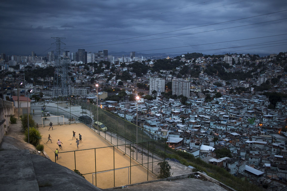 "Photo - In this March 7, 2014 photo, boys play soccer in the Sao Carlos slum after sunset in Rio de Janeiro, Brazil. The first thing Brazilian kids often do before pick-up games is play ""rock, scissors, paper"" to decide who will be goalkeeper. With so many outstanding strikers and midfielders in Brazilian history, few chose goalkeepers as their childhood idols. (AP Photo/Felipe Dana)"