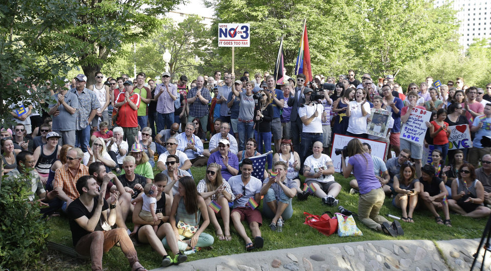 Photo - About 300 people gathered at a downtown park to celebrate the gay marriage ruling Wednesday, June 25, 2014, in Salt Lake City. A federal appeals court on Wednesday ruled for the first time that states must allow gay couples to marry, finding the Constitution protects same-sex relationships and putting a remarkable legal winning streak across the country one step closer to the U.S. Supreme Court. (AP Photo/Rick Bowmer)