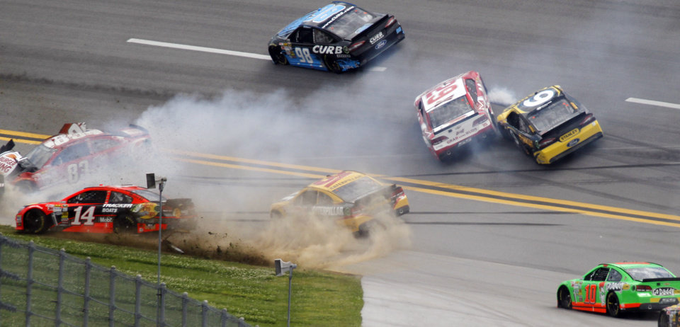 Photo - Cars spin through Turn one in a multi-car wreck during the NASCAR Sprint Cup Series Aaron's 499 auto race at Talladega Superspeedway in Talladega, Ala., Sunday, May 5, 2013. Pictured is: Tony Stewart (14), David Reutimann (83), Jeff Burton (31), Kevin Harvick (29), Marcos Ambrose (9) and Danica Patrick (10). (AP Photo/Butch Dill)