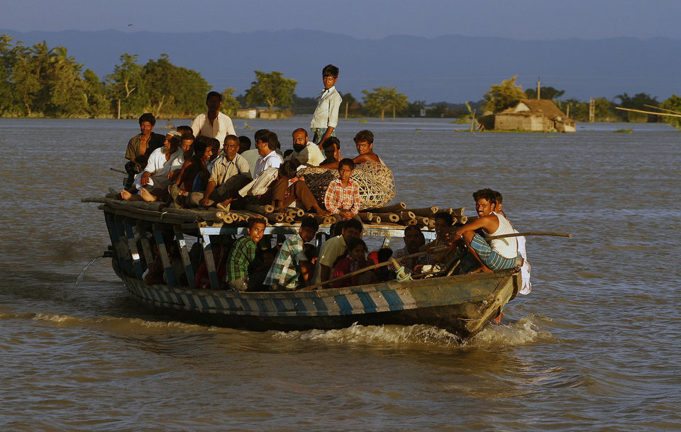 Photo -   Flood affected villagers crowd a boat in Gagalmari village in Assam state, India, Monday, July 2, 2012. The floods from monsoon rains in northeastern India killed dozens of people, with more than 2,000 villages inundated as rivers breached their banks, an official said Sunday. (AP Photo/Anupam Nath)