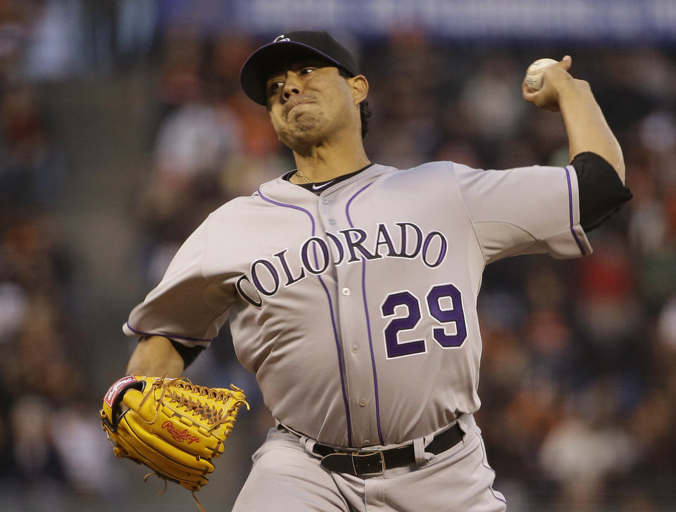 Photo - Colorado Rockies starting pitcher Jorge De La Rosa throws against the San Francisco Giants in the first inning of a baseball game Friday, April 11, 2014, in San Francisco. (AP Photo/Eric Risberg)