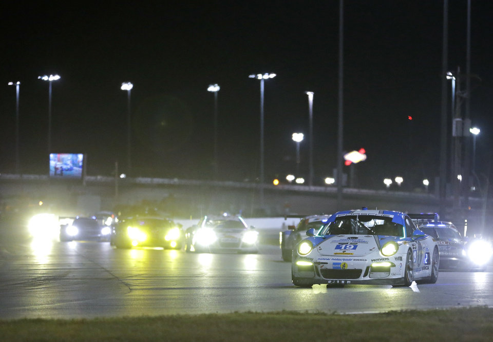 Photo - Jim Michaelian, front right, drives the Muehiner Motorsports Porsche 911 GT in the horseshoe turn followed by a group of cars during the IMSA Series Rolex 24 hour auto race at Daytona International Speedway in Daytona Beach, Fla., Saturday, Jan. 25, 2014. (AP Photo/John Raoux)