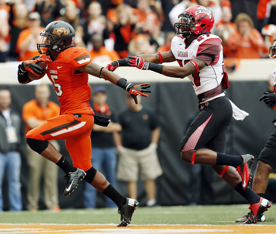 Photo - OSU's Josh Stewart (5) scores a touchdown in front of ULL's T.J. Worthy (27) in the second quarter during a college football game between Oklahoma State University and the University of Louisiana-Lafayette at Boone Pickens Stadium in Stillwater, Okla., Saturday, Sept. 15, 2012. Photo by Nate Billings, The Oklahoman