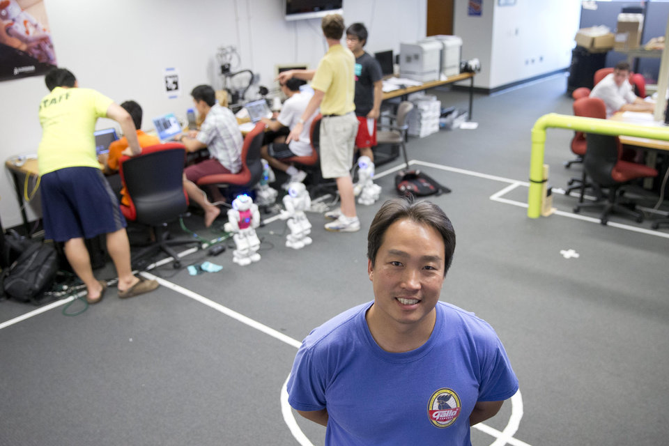 """Photo - In this July 7, 2014 photo, University of Pennsylvania engineering professor Dan Lee poses for a photograph as students prepare their robots for RoboCup in Philadelphia. Lee, who directs Penn's robotics lab in Philadelphia, has been the head """"coach"""" of the school's RoboCup soccer teams since 2002. Back then, the games resembled those played by 5-year-old children, Lee said. (AP Photo/Matt Rourke)"""