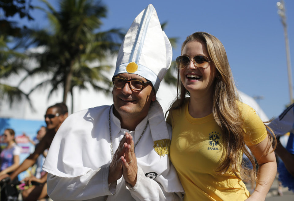 Photo - An Argentina soccer fan dressed as Pope Francis poses for a photo with a Brazil soccer fan before the start of the final World Cup match between Argentina and Germany, on Copacabana beach in Rio de Janeiro, Brazil, Sunday, July 13, 2014. (AP Photo/Silvia Izquierdo)