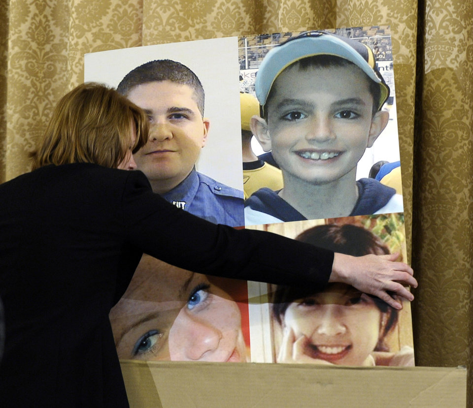 Photo - A poster board with photos of those who died in the Boston Marathon bombing is put away during the House Homeland Security Committee at a hearing on