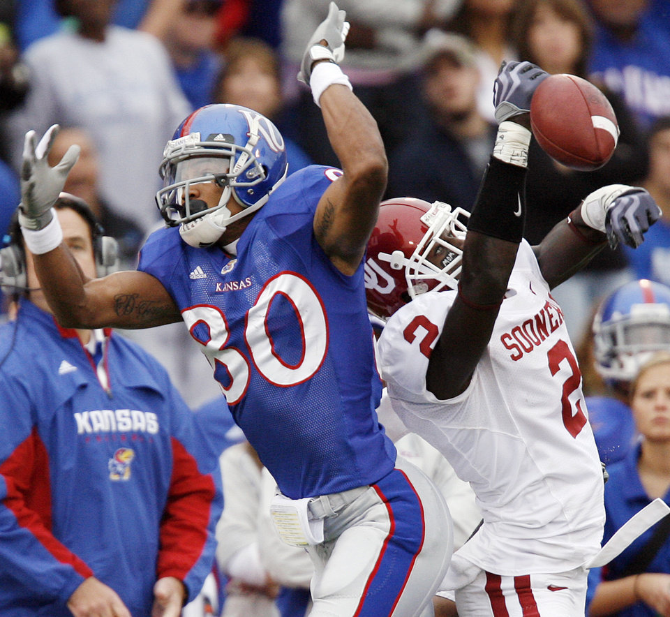 Photo - Oklahoma's Brian Jackson (2) breaks up a pass for Kansas' Dezmon Briscoe (80) during the second half of the college football game between the University of Oklahoma Sooners (OU) and the University of Kansas Jayhawks (KU) on Saturday, Oct. 24, 2009, in Lawrence, Kan. Oklahoma won the game 35-13. Photo by Chris Landsberger, The Oklahoman