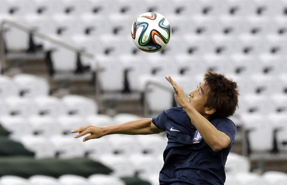 Photo - South Korea national soccer team player Koo Ja-cheol heads the ball during an official training session the day before the group H World Cup soccer match between South Korea and Belgium at the Itaquerao Stadium in Sao Paulo, Brazil, Wednesday, June 25, 2014. (AP Photo/Lee Jin-man)