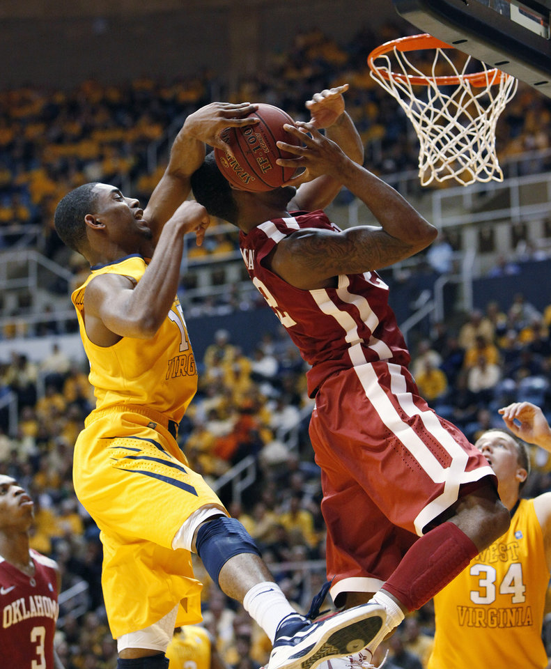 West Virginia's Terry Henderson, left, fouls Oklahoma's Amath M'Baye during the second half of an NCAA college basketball game Saturday, Jan. 5, 2013, in Morgantown, W.Va. Oklahoma won 67-57. (AP Photo/Randy Snyder)