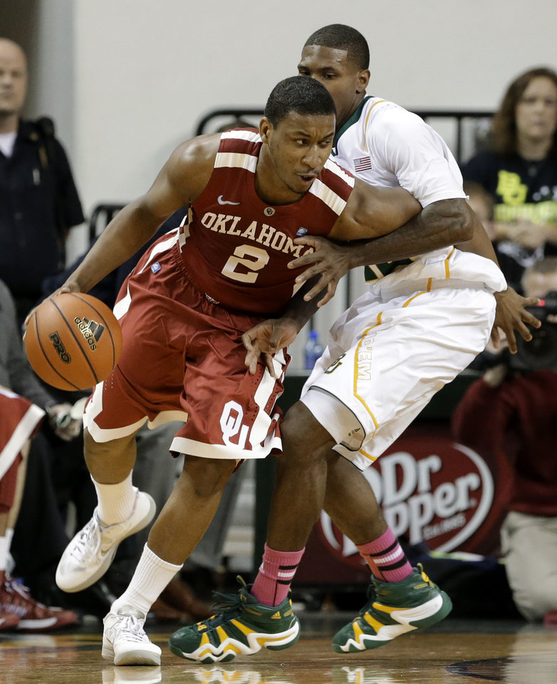 Photo - Oklahoma's Steven Pledger (2) attempts to get around Baylor's A.J. Walton, right, during the second half of an NCAA college basketball game Wednesday, Jan. 30, 2013, in Waco, Texas. Oklahoma won 74-71. (AP Photo/Tony Gutierrez) ORG XMIT: TXTG108