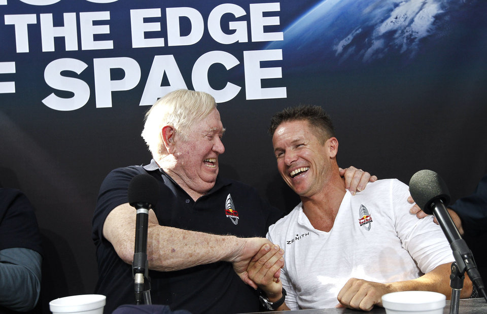 Felix Baumgartner, right, of Austria, shares a laugh with Col. Joe Kittinger, USAF retired, after successfully jumping from a space capsule lifted by a helium balloon at a height of just over 128,000 feet above the Earth's surface, beating Kittinger's old record of 102,799 ft., Sunday, Oct. 14, 2012, in Roswell, N.M. (AP Photo/Ross D. Franklin) ORG XMIT: NMRF132