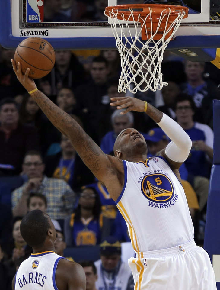 Photo - Golden State Warriors' Marreese Speights lays up a shot against the Denver Nuggets during the first half of an NBA basketball game on Wednesday, Jan. 15, 2014, in Oakland, Calif. (AP Photo/Ben Margot)
