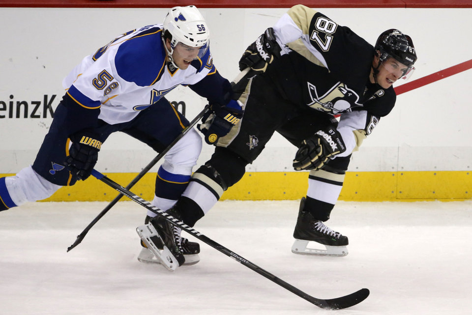 Photo - Pittsburgh Penguins' Sidney Crosby (87) is slowed down on a rush by St. Louis Blues' Magnus Paajarvi (56) in first period of an NHL hockey game in Pittsburgh, Sunday, March 23, 2014. (AP Photo/Gene J. Puskar)
