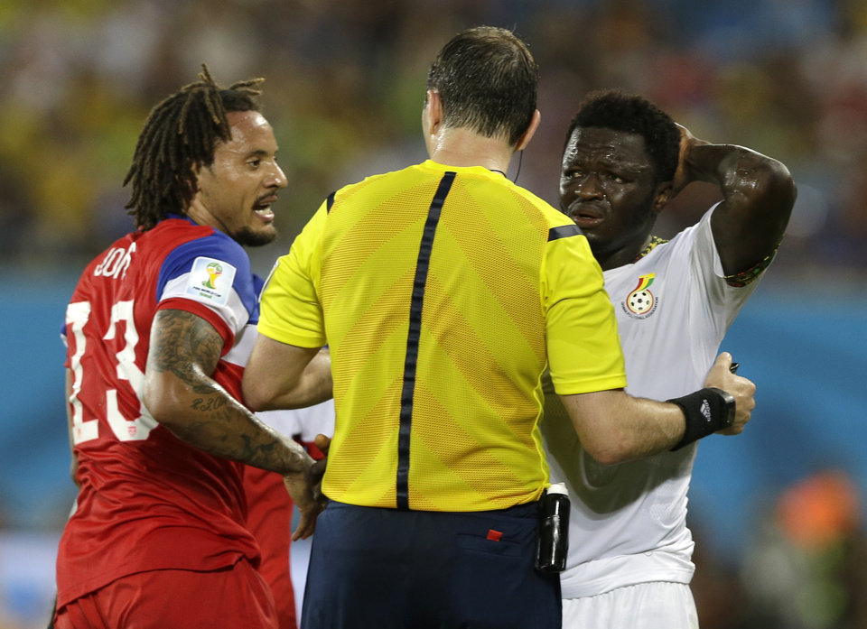 Photo - Referee Jonas Eriksson, centre,  from Sweden speaks to United States' Jermaine Jones, left, and Ghana's Sulley Muntari during the group G World Cup soccer match between Ghana and the United States at the Arena das Dunas in Natal, Brazil, Monday, June 16, 2014.  (AP Photo/Ricardo Mazalan)
