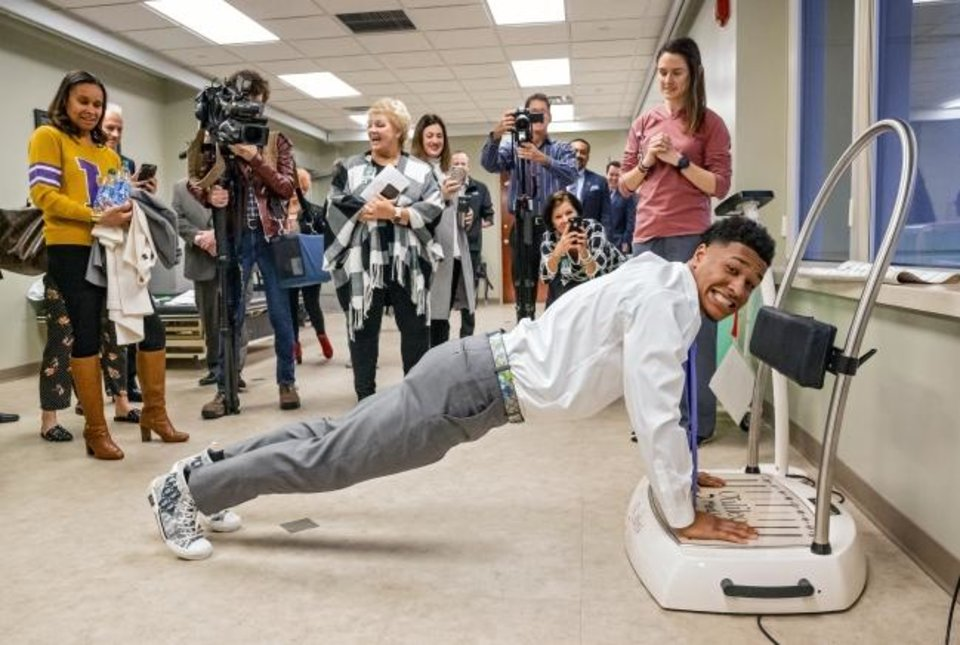 Photo -  LSU's Grant Delpit takes on a physical therapy plank challenge while he visits with patients at INTEGRIS Southwest Medical Center's Jim Thorpe Rehabilitation center on Tuesday. Delpit was in Oklahoma City to receive the Jim Thorpe Award as the nation's top college defensive back. [Chris Landsberger/The Oklahoman]