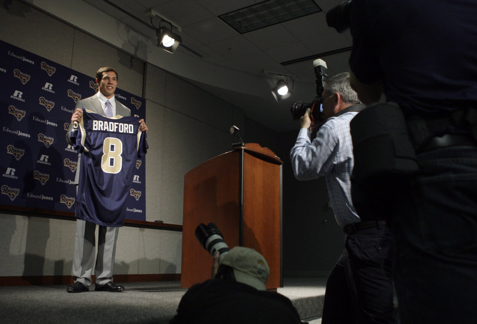 Photo - St. Louis Rams quarterback Sam Bradford poses for photographs with his new jersey during an NFL football news conference on Friday, April 23, 2010, at the Rams' training facility in St. Louis. Bradford was selected as the No. 1 overall pick by the Rams in the first round of the draft. (AP Photo/Jeff Roberson)  ORG XMIT: MOJR109