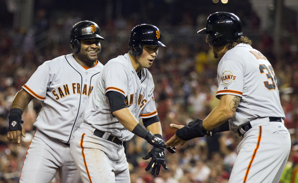 Photo - San Francisco Giants' Joe Panik, center, is congratulated by teammates Pablo Sandoval, left, and Michael Morse after hitting a three-run home run during the fourth inning of a baseball game against the Washington Nationals on Friday, Aug. 22, 2014, in Washington. (AP Photo/Evan Vucci)
