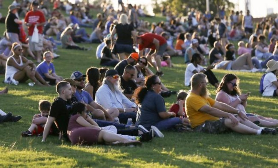 Photo -  People sit on the hill as Republican Hair performs during Friday's grand opening of Scissortail Park. [Nate Billings/The Oklahoman]