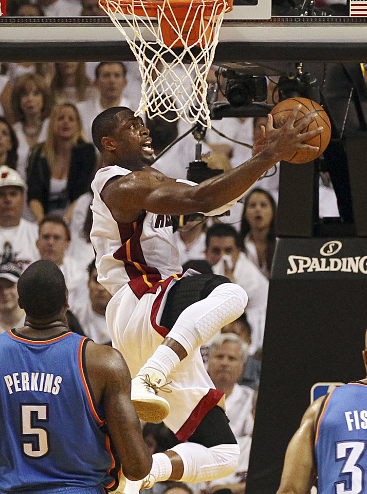 Miami Heat's Dwyane Wade goes to the basket against Oklahoma City Thunder's Kendrick Perkins (5) and Derek Fisher (37) in the second quarter of Game 3 of the NBA Finals basketball series, Sunday, June 17, 2012, in Miami. (AP Photo/El Nuevo Herald, Pedro Portal)  MAGS OUT ORG XMIT: FLMEH203