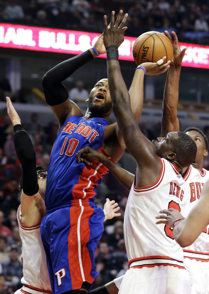 Photo - Detroit Pistons center Greg Monroe (10) shoots against Chicago Bulls guard Kirk Hinrich, left, forward Luol Deng (9) and guard Jimmy Butler during the first half of an NBA basketball game in Chicago, Sunday, March 31, 2013. (AP Photo/Nam Y. Huh)