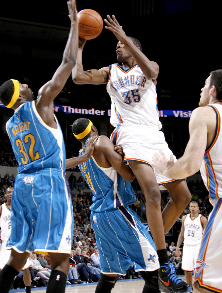 Photo - Oklahoma City's Kevin Durant runs into James Posey of New Orleans as Julian Wright defends during the NBA basketball game between the Oklahoma City Thunder and the New Orleans Hornets at the Ford Center in Oklahoma City on Friday, Nov. 21, 2008. Durant was called for an offensive foul on the play. BY BRYAN TERRY, THE OKLAHOMAN