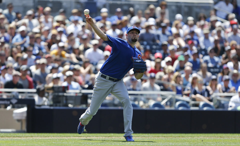 Photo - Chicago Cubs starting pitcher Jason Hammel fires a throw to first after fielding a bunt by San Diego Padres' Cameron Maybin during the fifth inning of a baseball game Sunday, May 25, 2014, in San Diego.  (AP Photo/Lenny Ignelzi)