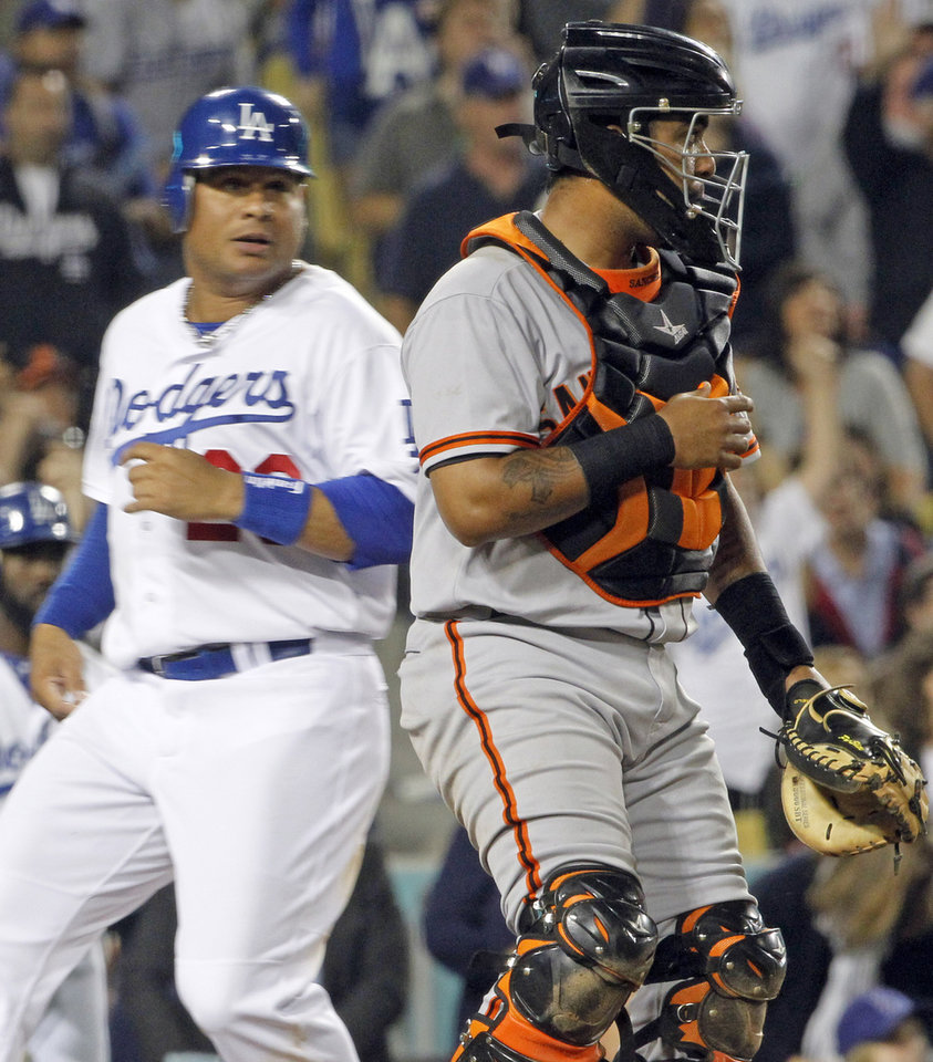 Photo -   The Los Angeles Dodgers' Bobby Abreu crosses the plate to tie the score, followed shortly by Juan Uribe for the go-ahead run as San Francisco Giants catcher Hector sanchez watches the infield in the sixth inning of a National League baseball game in Los Angeles Monday, May 7, 2012. The Dodgers won, 9-1 (AP Photo/Reed Saxon)