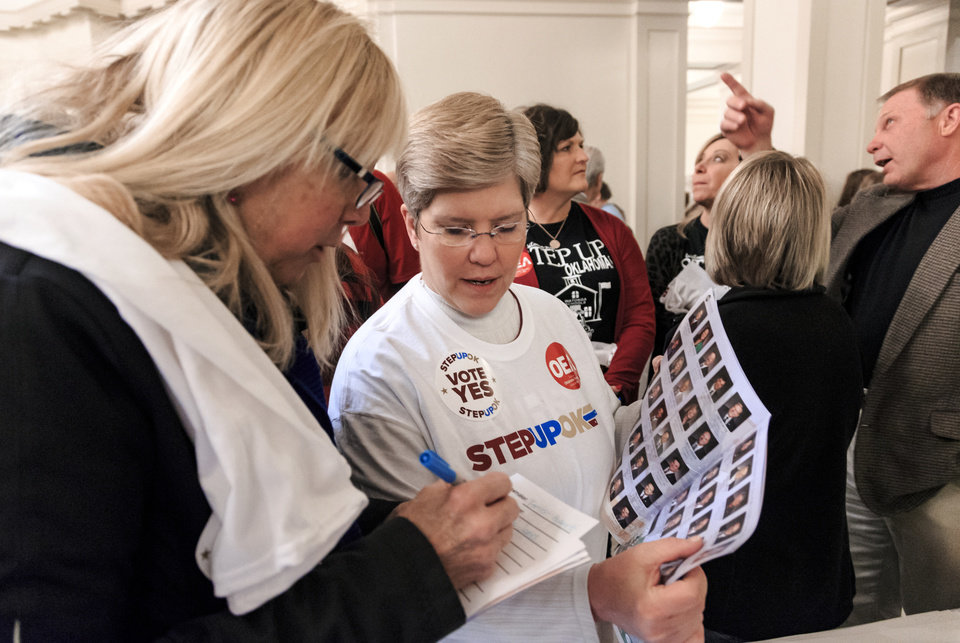 Photo - Edmond Public School teachers Leslie James, left, and Lorna Williams looks up their legislators during a rally to support the Step Up Oklahoma Plan at the state capitol in Oklahoma City, Okla. on Monday, Feb. 12, 2018.    Photo by Chris Landsberger, The Oklahoman