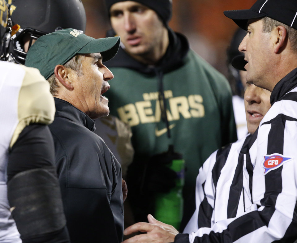 Photo - Baylor head coach Art Briles, left, talks with two officials in the second quarter of an NCAA college football game against Oklahoma State in Stillwater, Okla., Saturday, Nov. 23, 2013. (AP Photo/Sue Ogrocki)