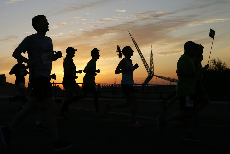 Photo - Runners are silhouetted with the Skydance Bridge in the background as the run south across the bridge over Interstate 40 at Walker Ave. at sunrise during the Oklahoma City Memorial Marathon in Oklahoma City, Sunday, April 28, 2019. [Nate Billings/The Oklahoman]