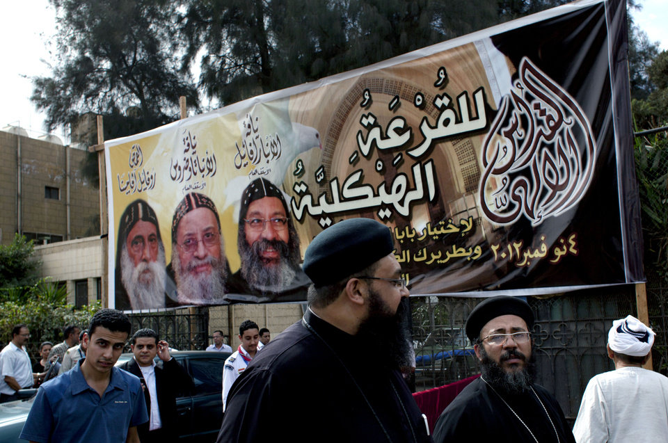 "Egyptian Copts and clergymen walk past an election poster with pictures and names of the three candidates, Father Raphael Ava Mina, left, Anba Tawadros, center and Anba Raphael, right and Arabic that reads ""the structural elections, November 4, 2012,"" following the papal election ceremony at the Coptic Cathedral in Cairo, Egypt, Sunday, Nov. 4, 2012. Egypt's ancient Coptic Christian church chose a new pope in an elaborate Sunday ceremony meant to invoke the will of God, in which a blindfolded boy drew the name of the next patriarch from a crystal chalice. Bishop Tawadros will be ordained Nov. 18 as Pope Tawadros II, the spiritual leader of a community that increasingly fears for its future amid the rise of Islamists to power in the wake of the 2011 ouster of longtime authoritarian leader Hosni Mubarak. (AP Photo/Nasser Nasser)"