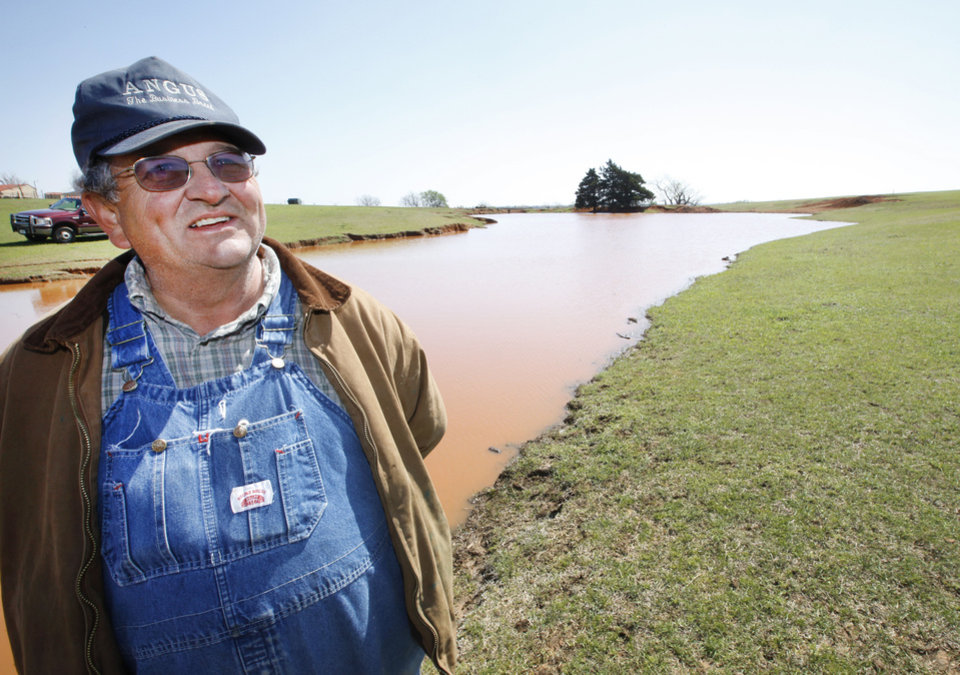 Above: John Pfeiffer�s ranch near Mulhall was so dry a few months ago that the dusty pond  bottom had a cow path through it. Recent rains have replenished the pond, shown here Wednesday, and eased Pfeiffer�s concerns about the future of his cattle herd.