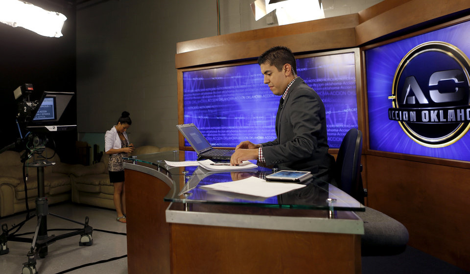 Photo - Ubaldo Martinez and Jessica Cano, left,   prepare for their Accion Oklahoma newscast on KTUZ-TV, a Telemundo affiliate in Oklahoma City, Wednesday, July 3, 2013. Photo by Bryan Terry, The Oklahoman