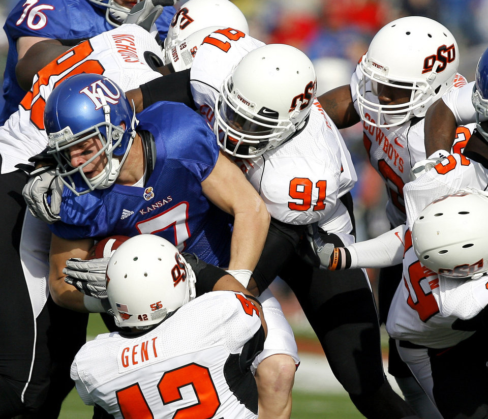 Photo - A host of OSU defenders takes down Kansas' Kale Pick (7) during the college football game between Oklahoma State (OSU) and Kansas (KU), Saturday, Nov. 20, 2010 at Memorial Stadium in Lawrence, Kan. Photo by Sarah Phipps, The Oklahoman