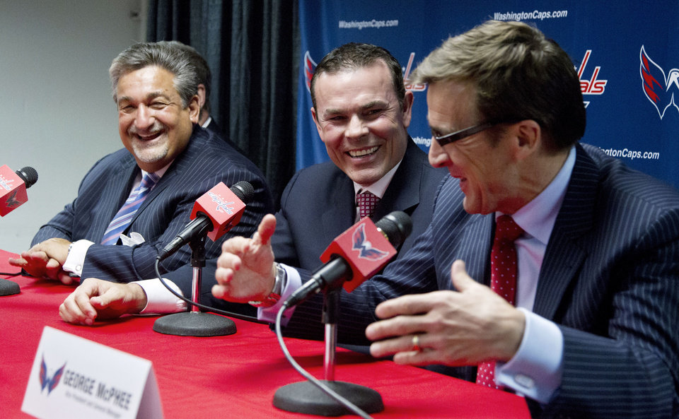 Photo -   Washington Capitals owner Ted Leonsis, left, coach Adam Oates, center, and general manager George McPhee smile during a news conference introducing Oates as the NHL hockey team's coach, in Washington on Wednesday, June 27, 2012. (AP Photo/Manuel Balce Ceneta)