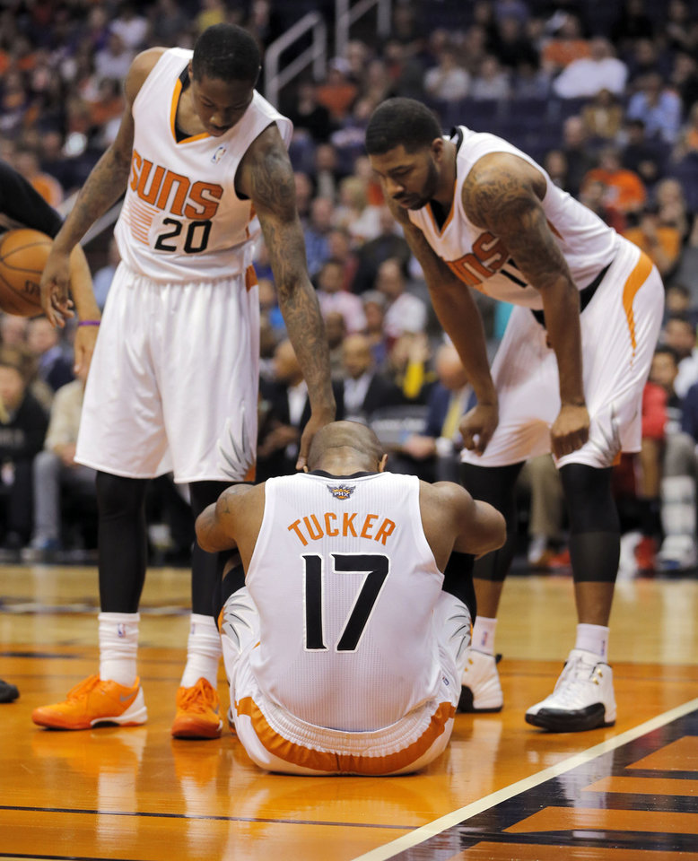 Photo - Phoenix Suns' P.J. Tucker (17) sits on the court after being injured as teammates Archie Goodwin (20) and Markieff Morris help him up against the  Milwaukee Bucks' during the first half of an NBA basketball game, Saturday, Jan. 4, 2014, in Phoenix. Tucker left the game. (AP Photo/Matt York)